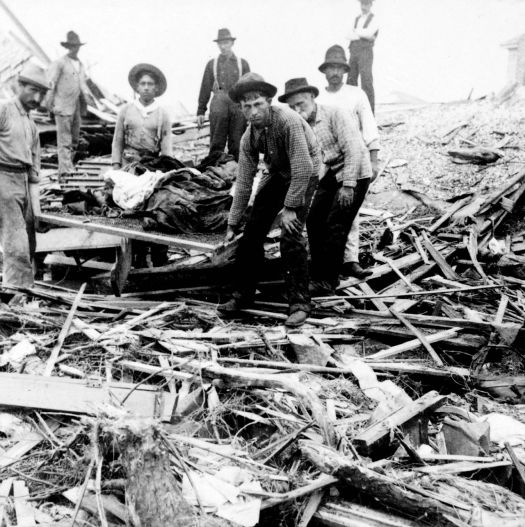 Survivors carry the dead out of the wreckage.